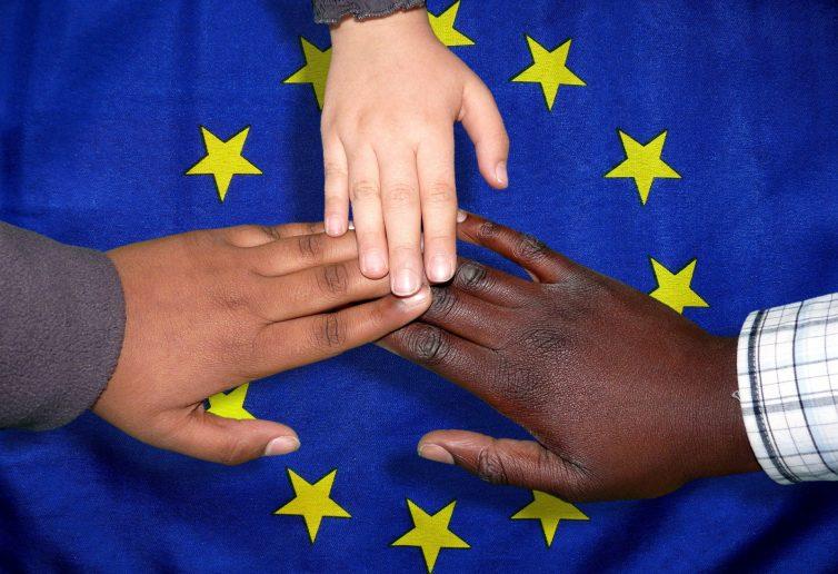manbi che si toccano su sfondo della bandiera europea