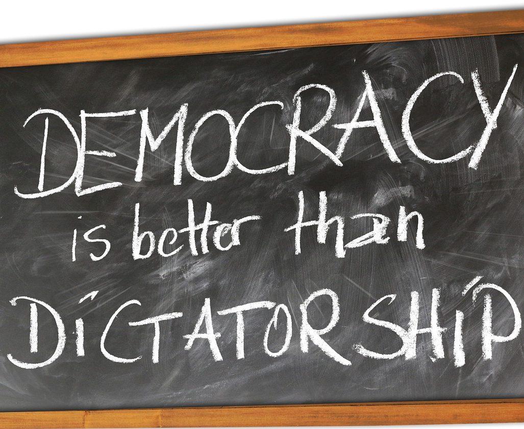 """Una lavagna con su scritto """"la democrazia è meglio della dittatura"""""""