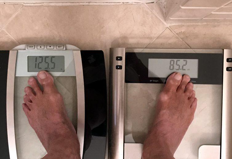 Una persona che si pesa su due bilance