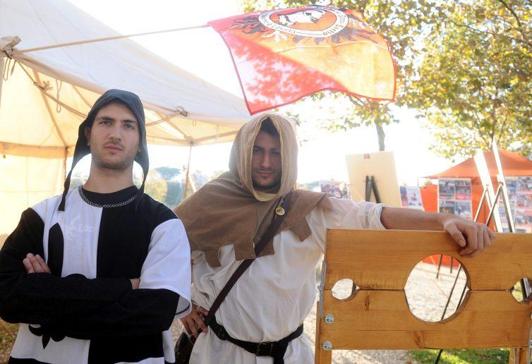 Due figuranti medievali con una gogna